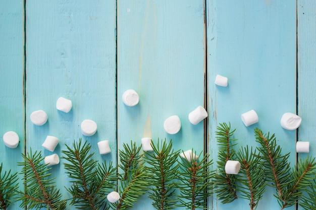 Fronteira de natal com galho de árvore do abeto e marshmallows em fundo de madeira