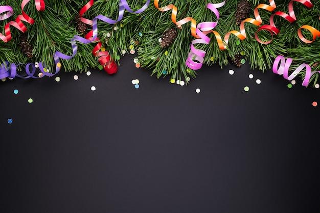 Fronteira de natal com pinheiros decorados ramos e confetes festivos em um fundo preto. copie o espaço para o texto