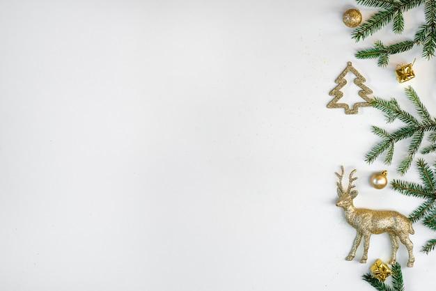 Fronteira de natal de ramos de abeto e brinquedos da árvore de natal de ouro sobre fundo branco, copiando o espaço. cartão de ano novo