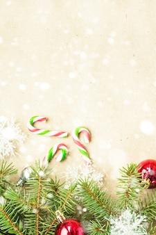 Fronteira de natal festivo com bolas vermelhas e prata em ramos de abeto e flocos de neve em fundo bege rústico de neve