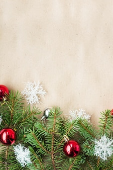 Fronteira de natal festivo com bolas vermelhas e prata em ramos de abeto e flocos de neve na superfície bege rústica