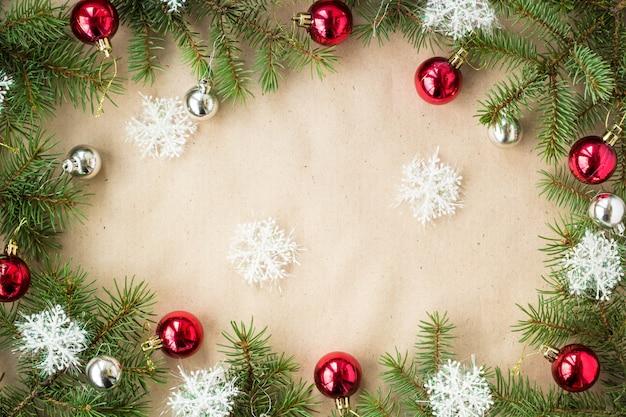 Fronteira de natal festivo com bolas vermelhas e prata em ramos de abeto e flocos de neve