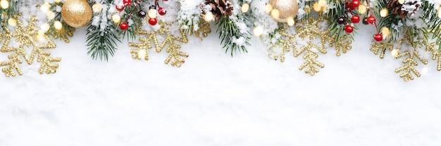 Fronteira de natal - galhos de árvores com enfeites dourados, bagas e flocos de neve na neve, plana leigos