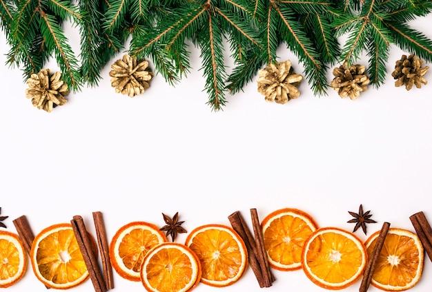 Fronteira de natureza natal de ramos de abeto e fatias de laranjas secas