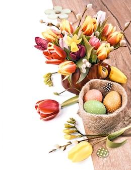 Fronteira de páscoa colorida com monte de tulipas e ovos na madeira