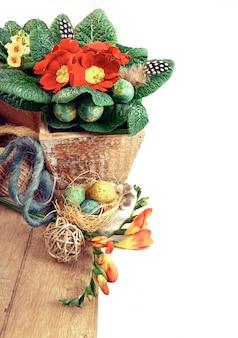 Fronteira de páscoa com flores de prímula, ovos e penas, espaço de texto