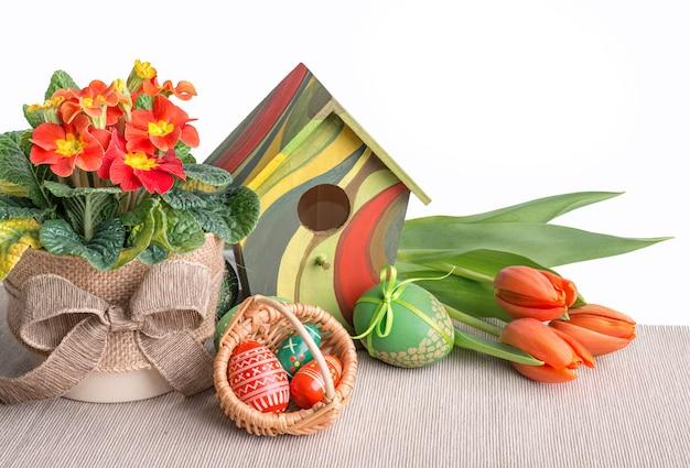 Fronteira de páscoa com tulipas laranja, prímula e decorações em branco