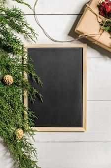 Fronteira de ramos de abeto e quadro de giz preto sobre fundo branco de madeira, bom para o cenário de natal. espaço livre para texto. vista do topo. copie o espaço. fechar-se