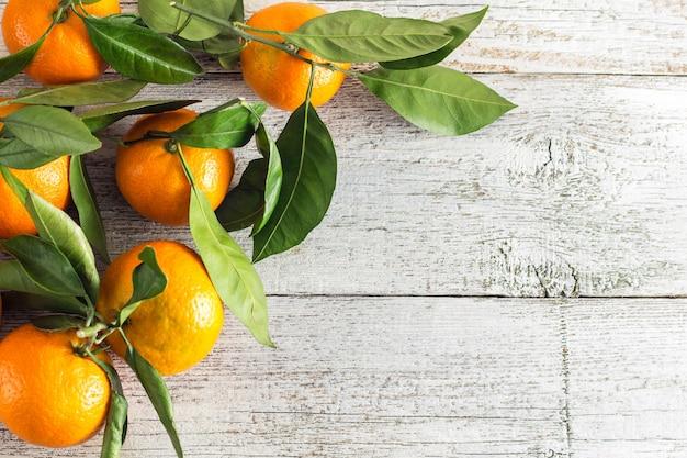 Fronteira de tangerinas laranja com folhas verdes sobre fundo branco de madeira. vista superior e espaço para cópia.