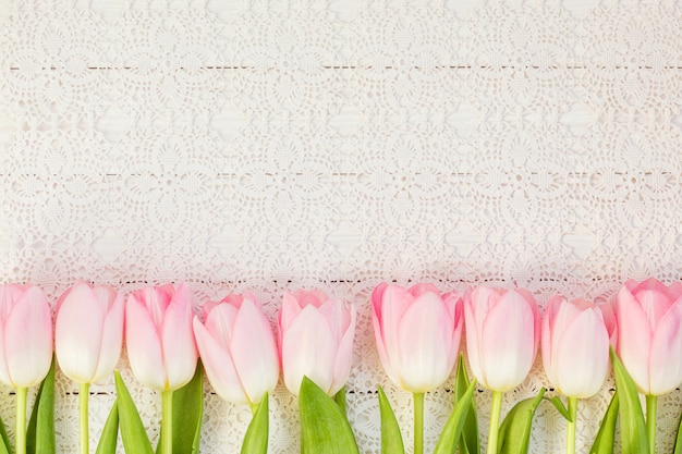 Fronteira de tulipas cor de rosa na toalha de mesa branca vintage