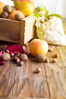 Fronteira outono de maçãs, peras e nozes na mesa de madeira velha.