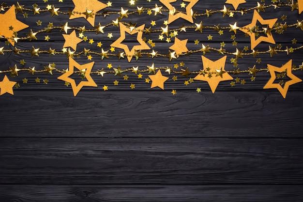 Fronteira plana leiga de estrelas grandes e pequenas de confete. contas de ouro em forma de estrelas.