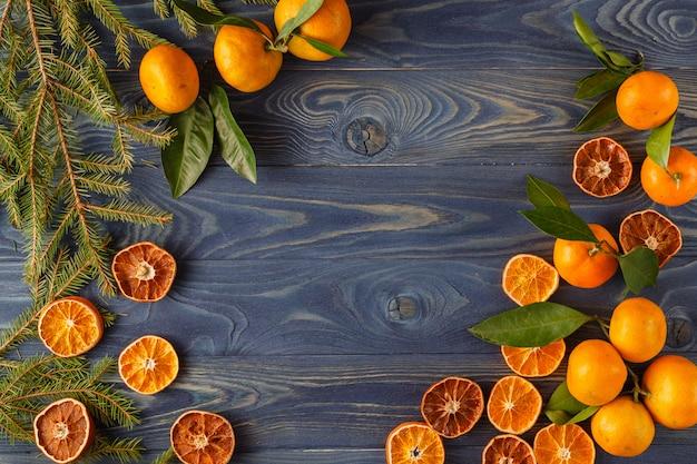 Fronteira, quadro de galhos de pinheiro de árvore de natal, fatia de fruta laranja seca no antigo fundo de mesa de mesa de madeira.