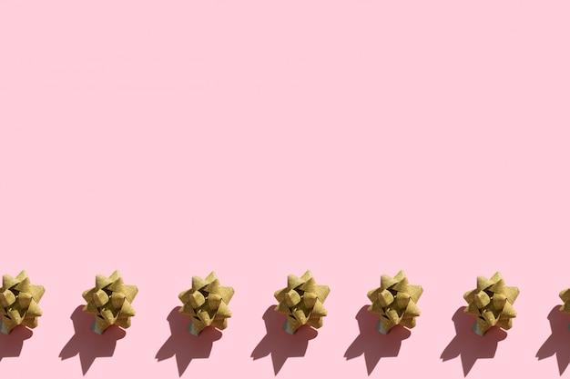 Fronteira sem costura de laços de fita ouro brilhante sobre um fundo rosa pastel