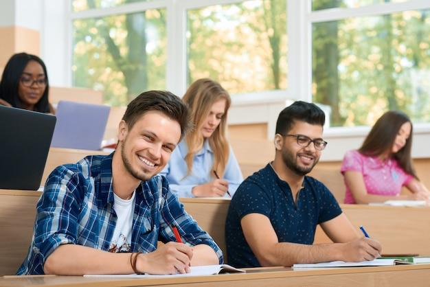 Frontview de studuing durante os estudantes da lição que olham a câmera.