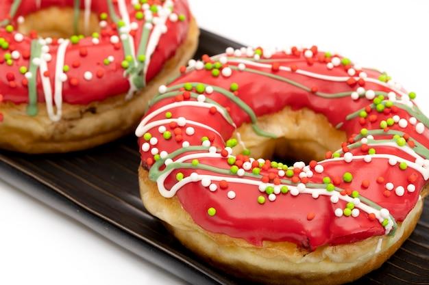 Frosted, glaceado e polvilhado com contas de açúcar, donuts em um prato marrom, vista de ângulo superior.