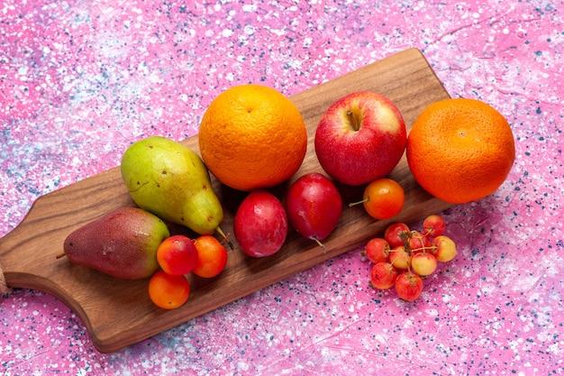 Frotn ver diferentes frutas composição tangerinas maçãs peras na mesa rosa.