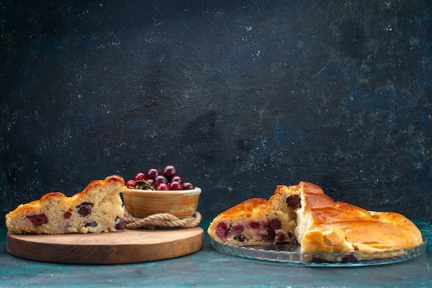 Frotn view deliciosa torta de cereja fatiada junto com ginjas vermelhas no escuro