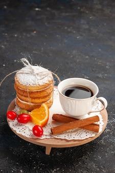 Frotn view sanduíche de biscoitos com frutas de canela e café na mesa escura.