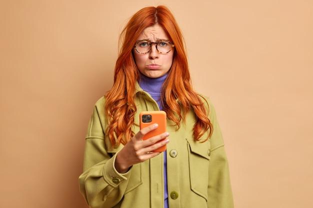 Frustrada, descontente, ruiva, européia, chateada porque o namorado não liga, fica ofendida, usa o celular para navegar na internet e usa uma jaqueta verde.