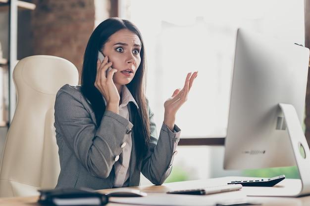 Frustrada garota colarinho chamar falar falar smartphone chefe ouvir horrível equipe despedir empresa informações sobre crise trabalhar computador remoto sentar mesa usar jaqueta blazer no local de trabalho estação de trabalho