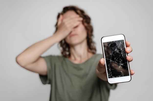 Frustrada jovem mulher encaracolada segurando o smartphone com o vidro da tela quebrada.