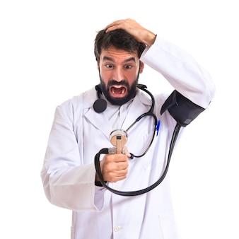 Frustrado médico com monitor de pressão arterial sobre fundo branco