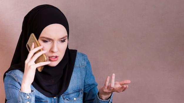 Frustrado; mulher árabe falando no smartphone, fazendo o gesto com a mão