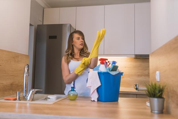 Frustrado, mulher, com, luvas borracha, e, avental, cesta segurando, com, materiais limpando