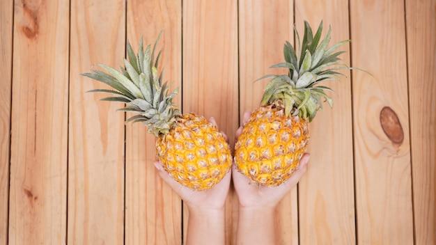 Fruta abacaxi na palma da mão sobre fundo de madeira