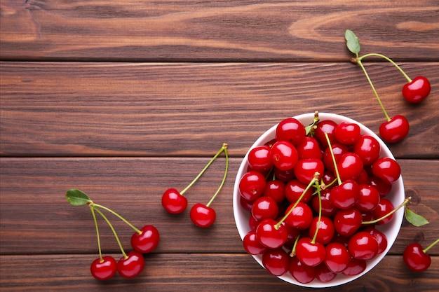 Fruta cereja vermelha fresca na mesa de madeira marrom