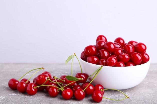 Fruta cereja vermelha fresca na tigela em concreto cinza