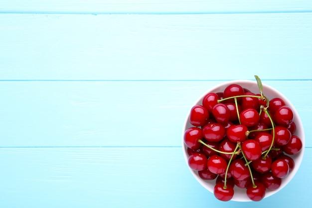 Fruta cereja vermelha fresca no prato na mesa de madeira azul