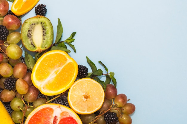 Fruta cítrica cortada ao meio; kiwi; amora e uvas em fundo azul