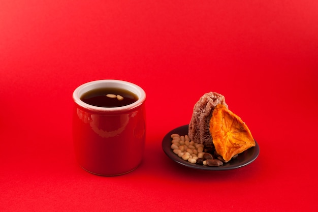 Fruta coreano punch-sujeonggwa sobre fundo vermelho. é feito de caqui seco com pinhão.