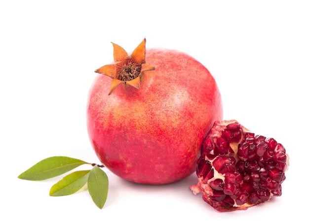 Fruta da romã com uma fatia isolada no fundo branco. trajeto de grampeamento incluído.