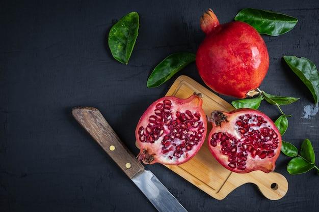 Fruta da romã cortada em um fundo preto