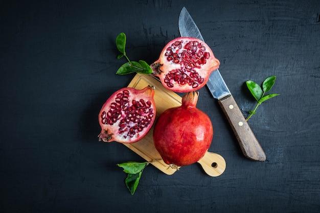 Fruta da romã cortada no fundo preto