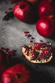 Fruta da romã. romã madura e suculenta na parede cinza rústica com espaço de cópia para o seu texto.