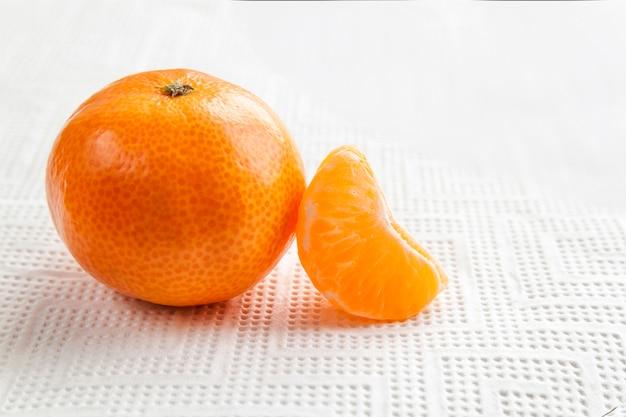 Fruta da tangerina ou do mandarino com a fatia isolada no fundo branco. peça alaranjada dos citrinos isolada no branco.