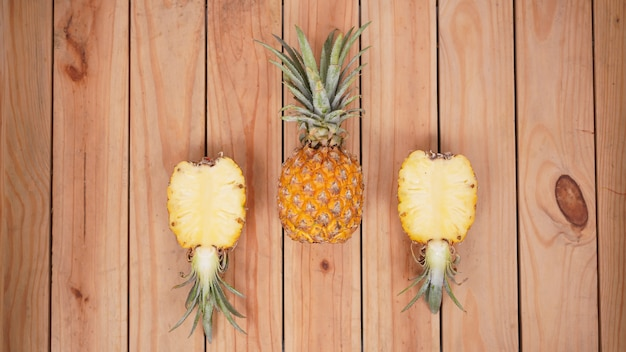 Fruta de abacaxi e seus pedaços em um fundo de madeira
