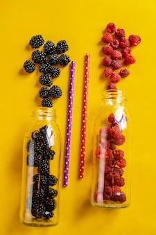 Fruta de amora e framboesa em garrafas de vidro com canudos