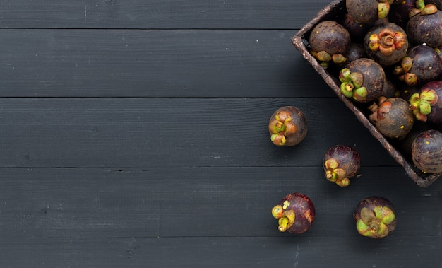 Fruta de mangostão closeup em madeira preta