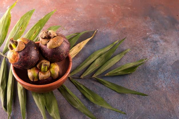 Fruta de mangostão na tigela de bambu