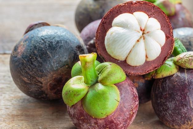 Fruta de mangostão no chão. descascados por carne branca no interior.