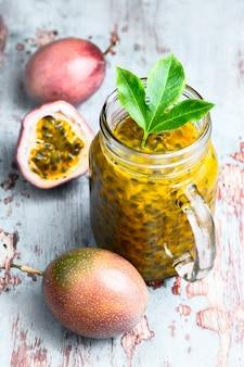 Fruta de paixão em um frasco de vidro com inteiro e meia fruta na mesa de madeira cinza.
