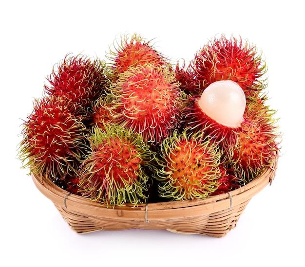 Fruta de rambutan em uma cesta em fundo branco