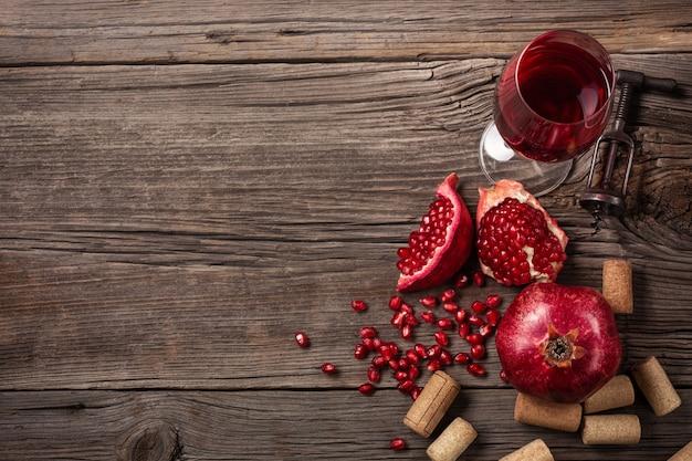 Fruta de romã madura com um copo de vinho e um saca-rolhas em um fundo de madeira