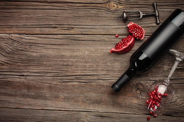Fruta de romã madura com um copo de vinho, uma garrafa e um saca-rolhas em um fundo de madeira