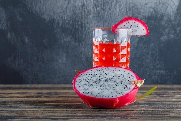 Fruta do dragão com suco na parede de madeira da tabela e do emplastro, vista lateral.